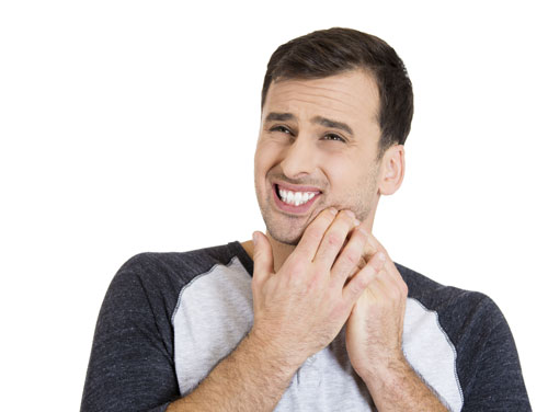 A man suffering from extreme tooth pain.